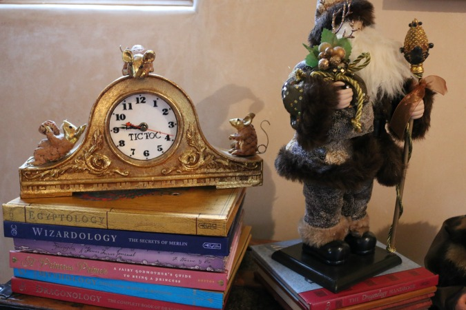 An adorable Christmas clock was displayed next to Santa Clause on a stack of books.