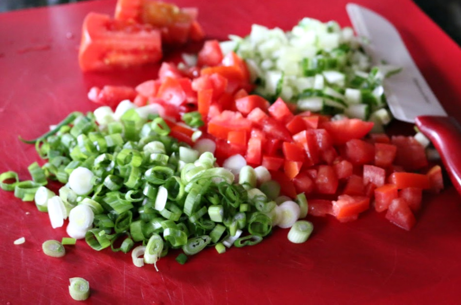 Chopped scallions, tomatoes, and cucumber for the Tabbouleh Salad)